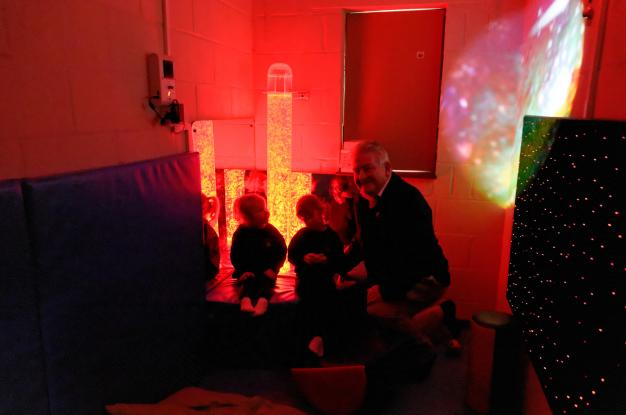 Lion President John Gee with two children in the Sensory Room